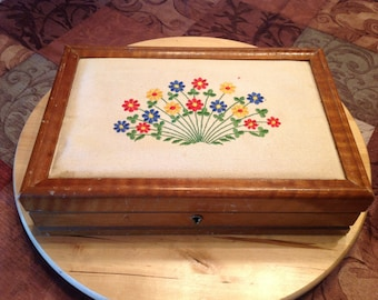 Wood jewelry box with upholstered lid.