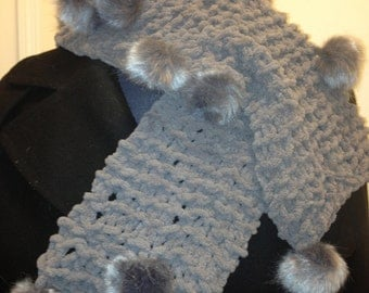 Soft, gray pom pom scarf that is approximately 43 inches long.