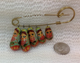 Vintage pin with 5 graduated colorful dolls.