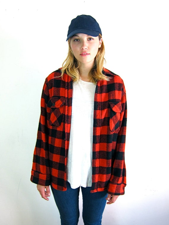 This versatile red and black plaid flannel jacket from Farmall IH features a drawstring jersey hood and copper snap front. Dual chest pockets, side zipper pockets, and taped logo detailing finish the look of this essential, quilt-lined jacket.