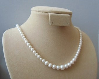 Graduated white cultured pearl necklace with silver rose clasp. 45 cm / 17.7'' in.