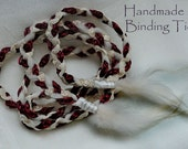 Handfasting cord in dark red burgundy and gold, with cream tulle and feather embellishments