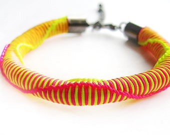 woven bracelet in neon pink with lime green and wave pattern