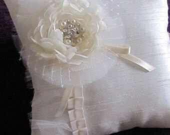 Isabella, a beautiful ivory chiffon camellia flower with a rhinestone and pearl center stand out on this pillow