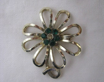 Gold tone vintage flower pin brooch with loopy petals and green rhinestone center