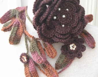 Crochet lariat with different shades of warm color leaves and  a  brown rose brooch.