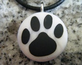 Dog Print hand carved on a polymer clay Mother of Pearl color background. Pendant comes with a FREE 3mm necklace