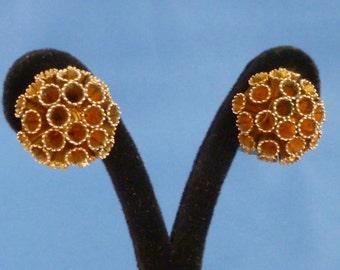 Gold tone tubular flower clip earrings.