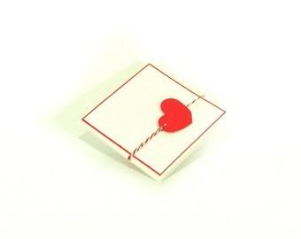 Handmade custom romantic folded wedding invitation, embossed background and red heart.