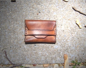 Leather Coin Pouch or pill pouch with strap closure in Rustic Brown. 3 x 2 inches in Full Grain Veg Tan leather handmade in the USA.