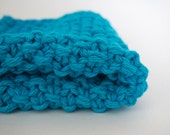 hand knit plushy textured cotton washcloth in bright aqua blue