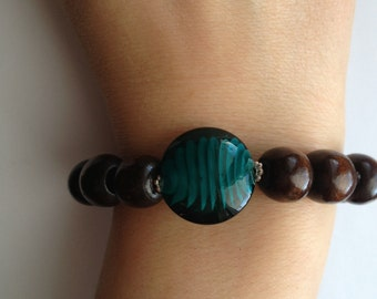 Nice wood beads bracelet with a dark green glass bead in the center