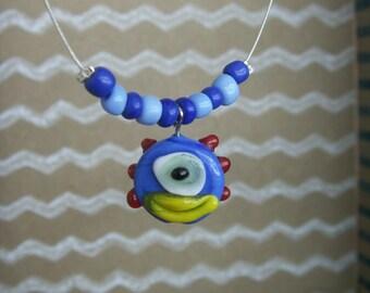Blue monster face necklace.