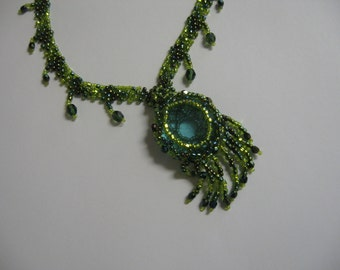 Plume de Paon (peacock feather): A signature glass medallion w/ a beaded ribbon of green glass beads and  accent drops