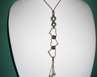 Necklace with brass hearts and shell pearls.