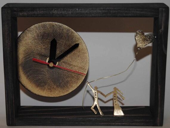 Desk bronze clock with ebony color wooden frame.