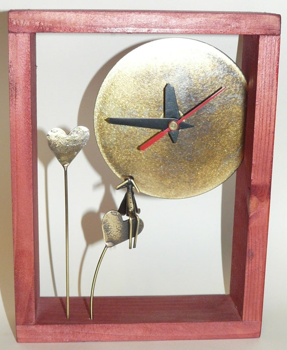 Desk bronze clock with light brown wooden frame.