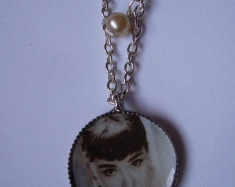 Silver toned pendant with a vintage photo of Audry Hepburn.