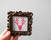 antlers . finished and framed cross stitch