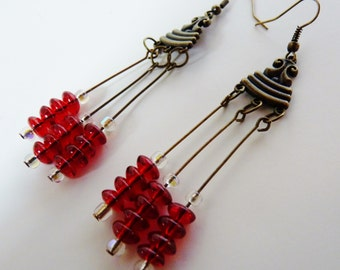 Antiqued brass connector holds 3 long dangles of ruby red roundels and seed beads.  antiqued brass ear wires, soho, boho, gypsy, bellydance