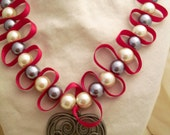 Heart pendant necklace with red ribbon and white and grey pearls.