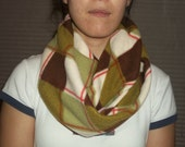 Plaid Argyle style infinity scarf. Brown, ivory, light and dark green with a red line running through.