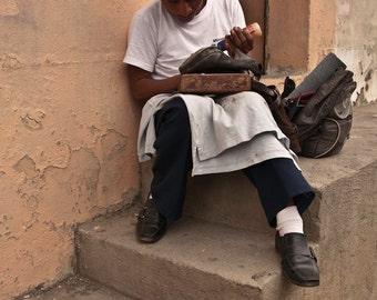 Shoe repair at the bordello in Quelzaltenango Guatemala- a color photograph