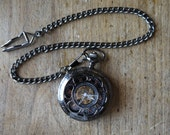 steampunk pocket watch with gears showing inner workings and movement. Hand wind up.