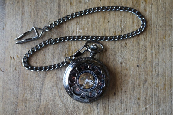 steampunk pocket watch with gears showing by ...