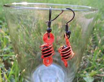 Orange twisted wire earrings with black bead