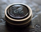 Figure 1: NOIR Solid Natural Perfume Round Tin - Rain, moistened dirt - Patchouli - Earthy, vegan musk - Grounding and evocative of Earth