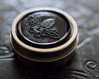 Figure 1: NOIR Solid Natural Perfume Round Tin - Notes of dark red wine, rain, and rich moistened dirt - Grounding and evocative of Earth