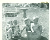 Summer Fun Little Boy Holding Baby in Bucket of Water Sleeping in Stroller 1950s  Vintage Black and White Photo Photograph