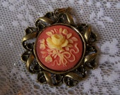 Round coral colored floral cameo in ornate setting - brooch or pendant