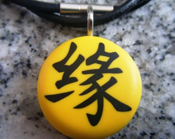 KARMA Japanese kanji symbol hand carved on a polymer clay sunny yellow color background.  Pendant comes with a FREE necklace