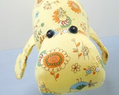 Yellow floral and bird print manatee stuffed animal
