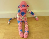 Pink, white, and blue argyle sock monkey doll with red heart