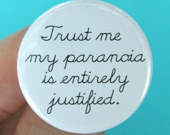 trust me my paranoia is entirely justified. 1.25 inch funny button. cursive.