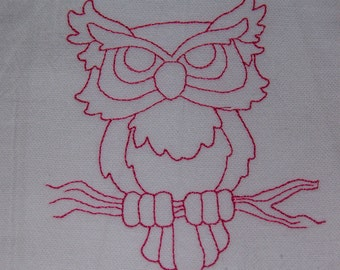 Pink owl sitting on a branch.