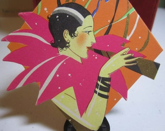 Colorful 1920's art deco die cut gold gilded Buzza bridge tally card lady with slicked back hair in elaborate costume blowing a party horn