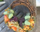 Dollhouse miniature wreath with apples, pears, grapes and metallic gold bow.