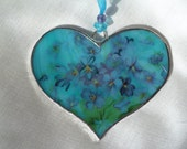 Streaky, iridescent sky blue and white, opaque stained glass heart decoration with pink poppies, forget-me-nots, violets and butterflies .