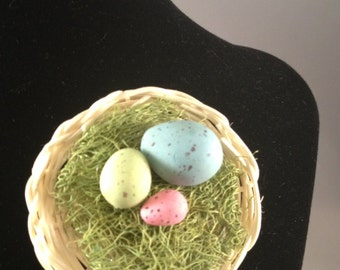 Birds nest pin with 3 minature eggs made of polymer clay.