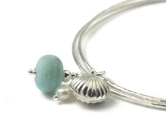 Charm Bangles | Sterling Silver Slim Bangles | Pale Blue Glass, Pearl and Silver Shell Charms | Coast Collection