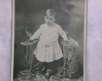 Cute Little Boy in White Dress - Boots - Wicker Chair - Antique Cabinet Photo
