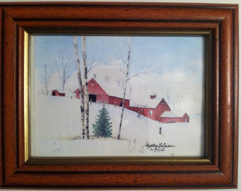 Framed watercolor print of Red Barns in the Snow.