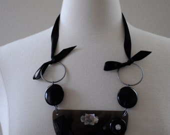 vintage 60s optic art geometric jewelry. satin ribbon tie with black and clear beads necklace.