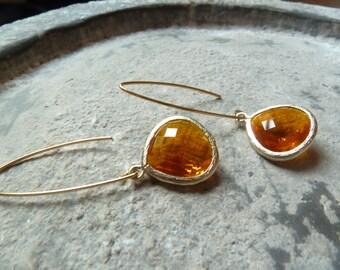 Hot orange teardrop earrings framed in textured  gold.