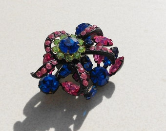 Vintage Austria crystal brooch in deep pink, peridot, and blue sapphire crystals Japanned metal