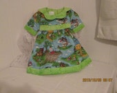 this adorable dress has a main fabric of 'nursery rhymes' with a flower collar , hem and sleeves made of green